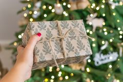 Hand som ut rymmer en gåva till julgranen Det nya året är 2019 vindträd i lantlig stil, gåva som binds med ett rep royaltyfri bild