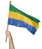 Hand som vinkar proudly nationsflaggan av Gabon Royaltyfri Bild