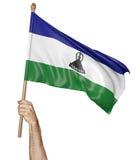 Hand som vinkar proudly nationsflaggan av Lesotho Royaltyfri Bild