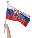 Hand som vinkar proudly nationsflaggan av Slovakien Royaltyfri Bild