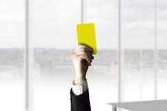 Hand som visar kontoret för gult kort Arkivfoto