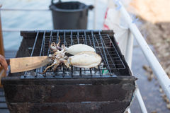 Hand of someone are grill fresh squid on hot stove with knife. Hand of someone are grill two fresh squid on hot stove with knife. this image for food and stock images