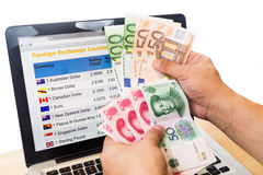 Hand sorting EURO and YUAN in front of currency exchange chart o Royalty Free Stock Images
