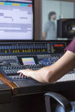 Hand of a sound engineer. Adjusting a sound mixing desk while a singer is rehearsing at the recording studio - focus on the hand Royalty Free Stock Images