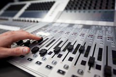 Hand on a sound fader in Television Gallery. Close-up of a hand on a fader on a Television studio mixing desk Royalty Free Stock Image