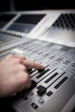 Hand on Sound Mixing desk in Television Gallery. Close-up of a hand on a fader on a television studio sound desk Stock Image