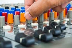 Hand on Soundboard - Stock Image. Hand making adjustment on an audio soundboard Royalty Free Stock Photos