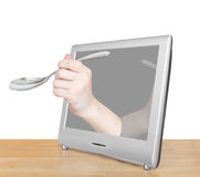 Hand with soup spoon leans out TV screen Royalty Free Stock Photo