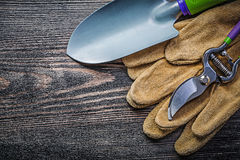 Hand spade secateurs safety gloves on wooden board Stock Images