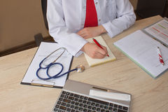 Hand of specialist on a prescription. Female medical doctor writing something sitting at her office Stock Photos