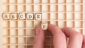 Hand spelling out the alphabet in wooden dice on a grid stock footage
