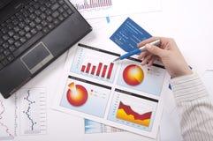 Hand spezifiziert das Finanzdiagramm, einen Arbeitsplatz Stockbilder