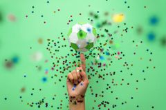 Hand spinning paper soccer ball on green background. Origami. Paper craft. Soccer game concept Stock Images