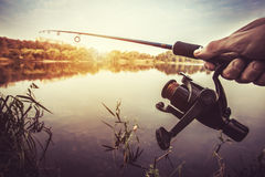 Hand with spinning and reel on the evening summer lake Royalty Free Stock Photography