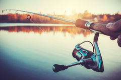 Hand with spinning and reel on the evening summer lake Royalty Free Stock Images