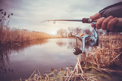 Hand with spinning and reel on the evening summer lake Royalty Free Stock Image