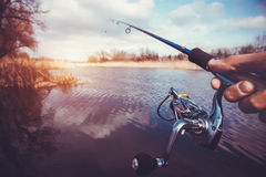 Hand with spinning and reel on the evening summer lake Stock Image