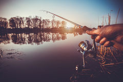 Hand with spinning and reel on the evening summer lake Stock Photos