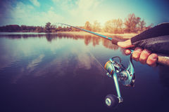 Hand with spinning and reel on the evening summer lake Stock Photo