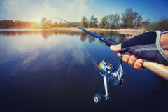 Hand with spinning and reel on the evening summer lake Royalty Free Stock Photos