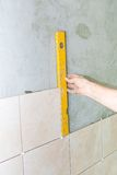 Hand with spirit level against gray wall with tiles Royalty Free Stock Image