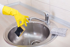 Hand with sponge above kitchen sink Royalty Free Stock Photography