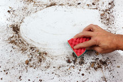 Hand with sponge wiping dirty surface Royalty Free Stock Images