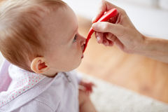 Hand with spoon feeding little baby at home Stock Photo