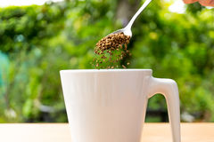 Hand with spoon put coffee in a cup Stock Image
