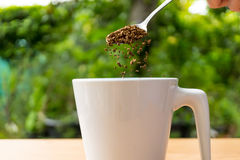 Hand with spoon put coffee in a cup Royalty Free Stock Photos