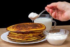 Hand with a spoon of sour cream and pancakes Stock Photography
