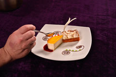 Hand with spoon takes from a classical orange cheese cake with c Royalty Free Stock Image