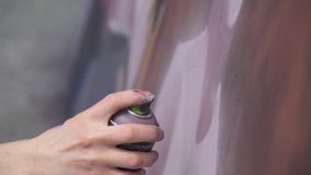 A hand with a spray can that draws a new graffiti on the wall. Photo of the process of drawing a graffiti on a wooden Royalty Free Stock Photo