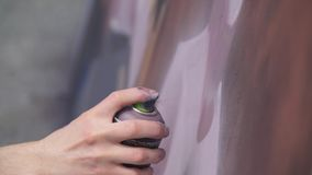 A hand with a spray can that draws a new graffiti on the wall. Photo of the process of drawing a graffiti on a wooden Stock Images