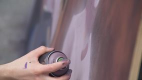 A hand with a spray can that draws a new graffiti on the wall. Photo of the process of drawing a graffiti on a wooden Stock Image