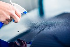 Hand spraying cleaning substance on the surface of a blue car. Close-up of hand spraying cleaning substance on the surface of a blue car at auto wash Stock Photos