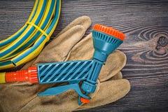 Hand spraying garden hose protective gloves on wooden board gard. Ening concept stock photo