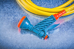 Hand spraying garden hose with spray nozzle on metallic backgrou. Nd gardening concept stock image