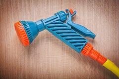 Hand spraying garden hose on wooden board gardening concept.  royalty free stock photo