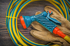 Hand spraying garden rubber hose safety gloves on wood board agr. Iculture concept royalty free stock image