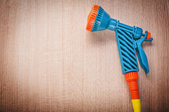 Hand spraying garden rubber hose on wood board gardening concept.  royalty free stock photography