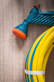 Hand spraying rubber garden hose with spray nozzle. On wooden board gardening concept royalty free stock photography