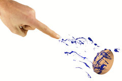 Hand sprays blue color on the egg Stock Photography