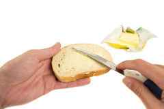 Hand spreading butter on slice of bread Stock Image