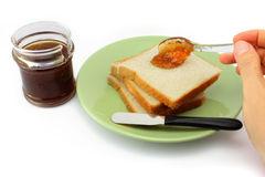 Hand spreads jam on fresh bread Royalty Free Stock Photo
