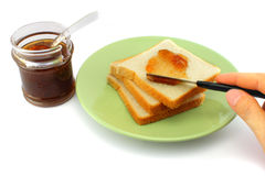 Hand spreads jam on fresh bread Stock Images