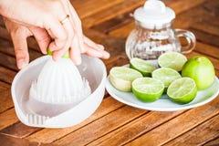 Hand squashing fresh lime Stock Photography