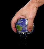 Hand squeeze earth. In a black background Stock Images