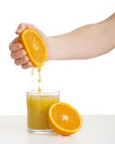Hand squeezes the juice from the orange. Woman's hand squeezes the juice from the orange into a glass stock photo