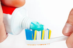Hand squeezes the toothpaste on the toothbrush on white background Royalty Free Stock Images